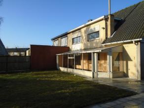 De woning omvat een inkom met trap naar boven, toilet, living, ingerichte keuken, garage, achterinkom/wasplaats, veranda, terras en tuin. Boven zijn e