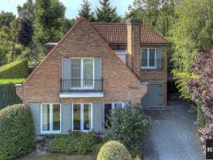 Rustig gelegen villa in groene omgeving op een perceel van 612m² met goede aansluiting naar E40/E17. Inkom, vestiaire, living met open haard en t