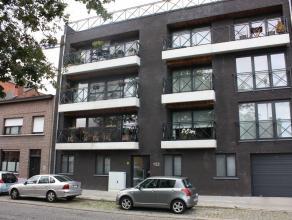 Recent 2 slaapkamer appartement 110m² in centrum Schoten met garage en kelderberging. Woonkamer in L-vorm aan ingerichte open keuken met bar-tabl