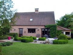Rustig gelegen landhuis met mooi aangelegde siertuin  Indeling: Gelijkvloers: inkomhal met gastentoilet en vestiaire, woonkamer met bibliotheek (56