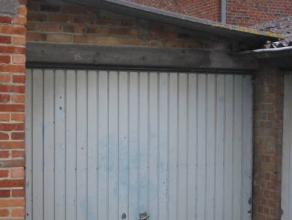 Garage ou remisebéton au sol et porte basculanteavec parking gravier grisdans une cour de batterie de garages surveill&eacute