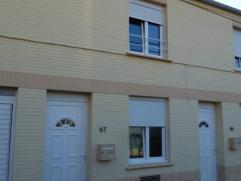 Maison unifamiliale composée de deux chambres, salon, salle à manger, cuisine équipée, salle de douche, garage, grenier et