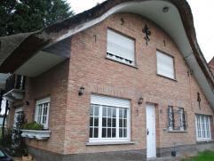 Située dans une rue calme, cette jolie villa au toit de chaume offre en son rez-de-chaussée un hall avec escalier apparent, un grand liv