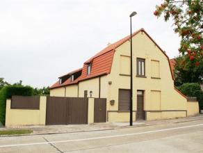 Zeer grote woning met garages, atelier en heel grote tuin, bestaande uit: inkomhal, salon, living, half-ingerichte keuken, badkamer, 5 kamers, bureau,