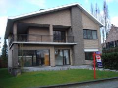 Ruime villa in een zeer rustige straat op wandelafstand van de International School te Ekeren. Inkomhal met tegelvloer en trap naar verdieping. Bureel