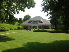 Rustig en toch centraal gelegen luxe villa met o.a. 4 slk, 2 badkamers, inpandige garage en verwarmd buitenzwembad op een perceel van ca. 3.000 m2 met