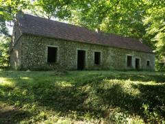 Au coeur d'un terrain boisé d'un hectare nonante centiares, très beau bâtiment en pierre en gros oeuvre non fermé, partiell