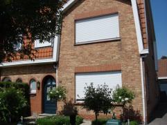 Gezellig en centraal gelegen woonhuis met garage en tuin. Inkomhal, gastentoilet, living in masief parket met open haard en veranda, open ingerichte