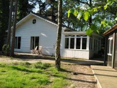 Een houten woning in bosrijke omgeving. De woning beschikt mogelijk over 3 slaapkamers. Indeling: ÂWoonkamer met allesbrander en voorzien van ee