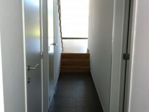 Inkomhal op zwarte tegels met inbouwspots en apart toilet. Open keuken met ruime eethoek/kamer die zicht geeft op de tuin, keuken is voorzien van ijsk