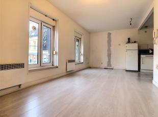 Appartement situé dans une zone à caractère commercial comprenant un living ouvert sur une cuisine avec armoires de rangement (&e