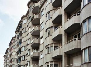 Appartementsblok in na-oorlogse modernistische stijl. Hall in travertin, vestiaire, grote living in parket met open haard, ingerichte keuken, terras 1