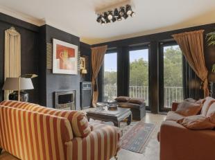 Men betreedt het appartement via de inkomhal met beveiligde deur en kan zo door naar de grote, L-vormige woonkamer op parket met houten balken. Een ge