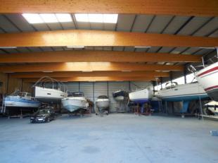 Dit bedrijfsgebouw, bestaande uit een magazijn van 1.395 m² en kantoren van 270 m², is gelegen in het havengebied aan het veer van Langerbru