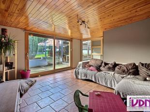 Grande maison semi-mitoyenne avec jardin composée d'un salon, d'une véranda, d'une cuisine équipée semi-ouverte sur la sal