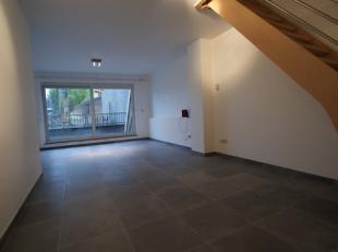 Triplex-appartement met terras in centrum Overijse. 1ste verdieping: Inkomhal, apart toilet, 35m² woonkamer met terras (12m²), ingerichte ke