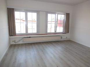 Inkomhal op beige tegels met inbouwspotjes, living op nieuwe laminaatvloer, witte keuken met geïntegreerde koelkast, gaskookplaat, oven en afzuig